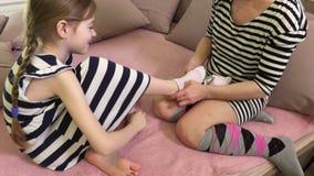 Kvinnan hjälper dottern till pålagda sockor stock video