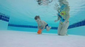 Kvinnan hjälper ett barn att lyfta en leksak från botten av simbassängen stock video