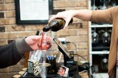 Kvinnan häller exponeringsglas av rött vin Arkivbild