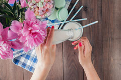 Kvinnan häller mjölkar i exponeringsglas Arkivfoto