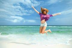 Kvinnan hoppar för glädje på den vita sandstranden Royaltyfri Bild