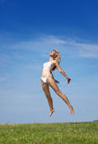 Kvinnan hoppar i ett sommargräsplanfält Arkivbilder