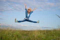 Kvinnan hoppar i fält för grönt gräs Fotografering för Bildbyråer
