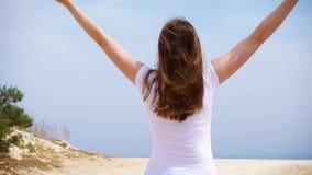 Kvinnan hoppar med glädje längs sandbanan Bekymmerslös kvinnlig som lyfter upp armar och dansar i ultrarapid