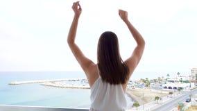 Kvinnan hoppar med glädje på terrass med havssikt Enfaldiga kvinnliga lönelyftarmar up och dansar i ultrarapid lager videofilmer