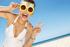 Kvinnan i ananasexponeringsglas som visar seger, gör en gest på stranden Royaltyfri Fotografi