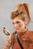 Kvinnan i apelsin och brunt utrustar, ståenden, krigaren, mode fotografering för bildbyråer