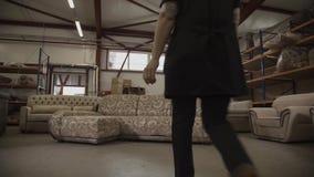 Kvinnan i arbetslikformig kommer till en soffa och tar delen av i möblemangfabriken lager videofilmer