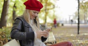 Kvinnan i basker som använder smartphonen parkerar in stock video