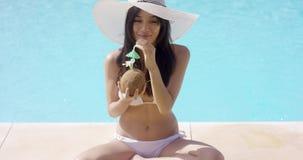 Kvinnan i bikini- och solhatt sitter korsat lagt benen på ryggen stock video