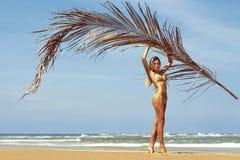 Kvinnan i bikini poserar på stranden nära havet med gömma i handflatan filialen ö phuket thailand Arkivfoto