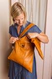 Kvinnan i blått klär blickar in i ett ljus - brun handväska Royaltyfria Bilder
