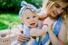 Kvinnan i blåttklänning lyfter upp hennes lilla dotter i den samma kläderna royaltyfri foto