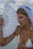 Kvinnan i brud- skyler med fanen Fotografering för Bildbyråer
