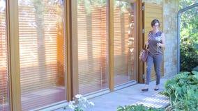 Kvinnan i byxa och blus med en selfiepinne går vidare dörren stock video