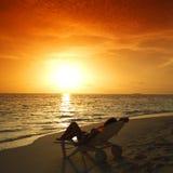 Kvinnan i chaise-varar slö att koppla av på strand arkivfoto