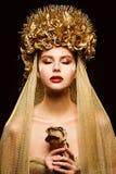 Kvinnan i den guld- blommakronan, modemodellen Beauty Makeup, brud i guld- skyler att rymma rosen arkivfoton