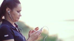 Kvinnan i den ljudsignal hörlurar gör behandligar med smartphonen lager videofilmer