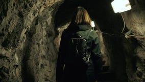 Kvinnan i den mörka grottan med ryggsäckturisten följer tillbaka sikt scenistflicka mellan stenväggen arkivfilmer