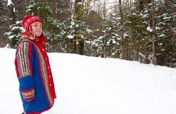 Kvinnan i den Saami hatten och blått klädde med filt täcker Arkivfoton