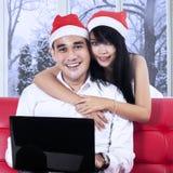Kvinnan i den santa hatten omfamnar hennes make Fotografering för Bildbyråer