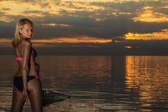 kvinnan i den svarta bikinin som poserar på en sand, vaggar Royaltyfri Fotografi