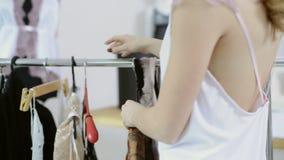 Kvinnan i den vita nattlinnen kommer att rack med hängare väljer transperent lager videofilmer