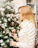 Kvinnan i den vita tröjan står nära en julgran royaltyfria foton
