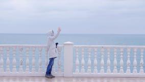 Kvinnan i det vita omslaget och huven gör selfievideoen på smartphonen på härlig terrass med havssikt på strand sida arkivfilmer