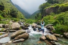 Kvinnan i det yogaasanaVrikshasana trädet poserar på vattenfallet utomhus Arkivbild