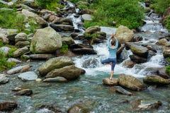 Kvinnan i det yogaasanaVrikshasana trädet poserar på vattenfallet utomhus royaltyfria foton
