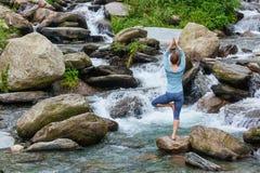 Kvinnan i det yogaasanaVrikshasana trädet poserar på vattenfallet utomhus fotografering för bildbyråer