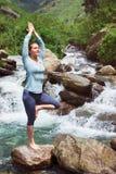 Kvinnan i det yogaasanaVrikshasana trädet poserar på vattenfallet utomhus arkivfoto