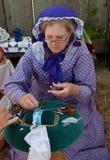 Kvinnan i dräkten för det 19th århundradet som gör spolen, snör åt Royaltyfri Fotografi