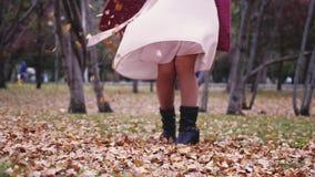Kvinnan i en beige klänning som kastar sidor i en höstnedgång, parkerar Sikt av henne ben Royaltyfri Fotografi