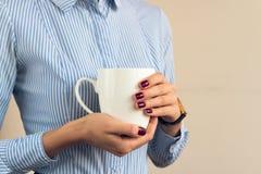 Kvinnan i en blå randig skjorta rymmer en vit kopp royaltyfria foton