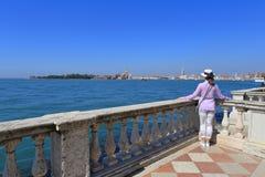 Kvinnan i en hatt står benägenhet på balustraden och ser staden av Venedig Royaltyfri Bild