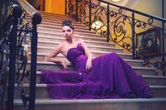 Kvinnan i en lång klänning sitter på trappan Arkivbild