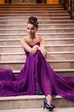Kvinnan i en lång klänning sitter på trappan Arkivfoto