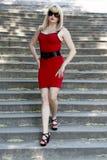 Kvinnan i en röd klänning går ner på moment Fotografering för Bildbyråer