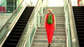 Kvinnan i en röd klänning och en hatt går uppför trappan på flygplatsen Flygplats Kvinnan i en hatt och med en ryggsäck går arkivfilmer