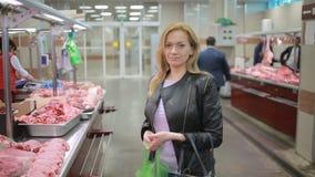 Kvinnan i en supermarket bredvid en kötträknare, köpande kött, ser kameran stock video