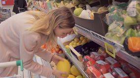 Kvinnan i en supermarket på grönsakhyllashoppingen för livsmedel, kontrollerar han ut livsmedlet stock video