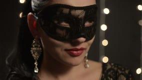 Kvinnan i en Venetian maskering på bakgrunden av natten tänder, närbilden stock video