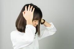 Kvinnan i en vit klänning är det rörande huvudet som visar hennes huvudvärk Orsaker kan orsakas av spänning eller migrän royaltyfria foton