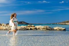 Kvinnan i en vit klänning kör på vattnet Royaltyfria Foton