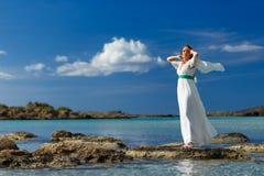 Kvinnan i en vit klänning på vaggar i havet Arkivbilder