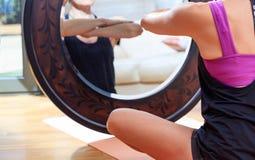 Kvinnan i en yoga poserar framme av en spegel royaltyfri foto