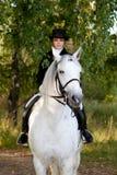Kvinnan i enhetlig ritt på den vita hästen parkerar in Royaltyfri Foto