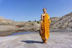 Kvinnan i etnisk klänning går för vatten fotografering för bildbyråer